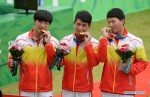 Chinese athletes Yong Zhiwei (L), Qi Kaiyao (C) and Gu Xuesong pose on the podium during the awarding ceremony of the recurve men's team match of archery at the 17th Asian Games in Incheon, South Korea,