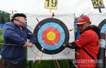 Staff clear a target at the 1st 'Li Guang Cup' International Archery Tournament, in Gansu.